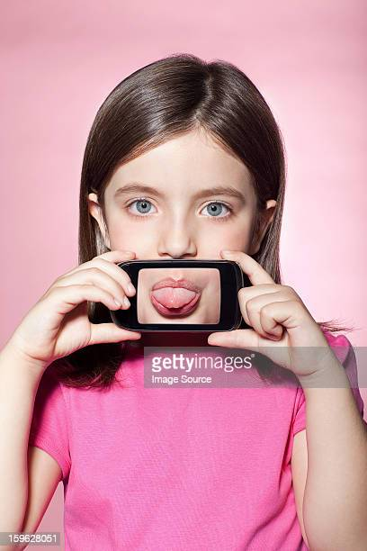 Girl holding smartphone over mouth, sticking out tongue