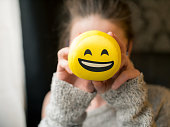 Girl holding smiley face laughing emoticon in front of her face. The young woman is of caucasian ethnicity and is casually dressed. The scene is situated indoors in a city apartment in Sofia, Bulgaria