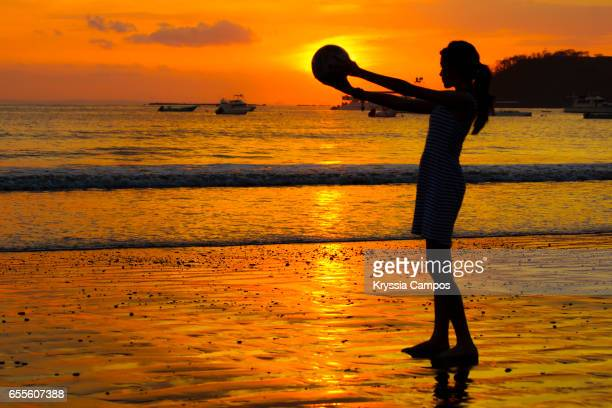 Girl holding soccer ball against the sun during sunset at the beach