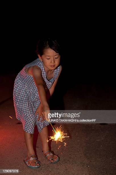 Girl Holding Sparkler at Night