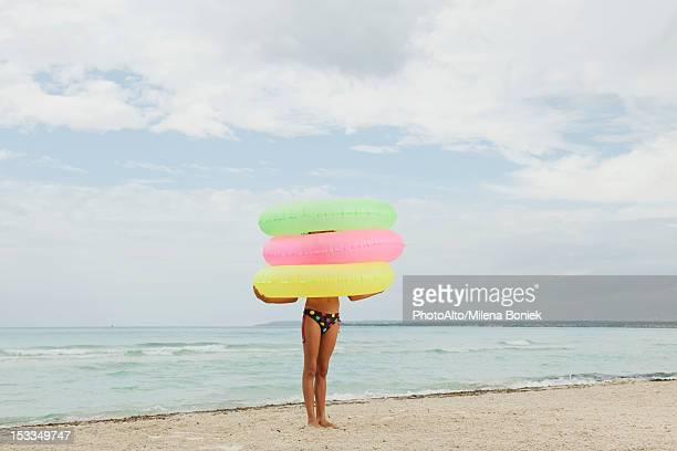 Girl holding stack of inflatable rings on beach, face obscured