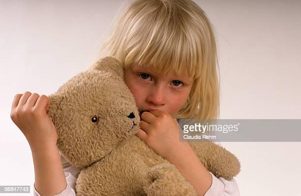 Girl (3-5) holding teddy bear, portrait