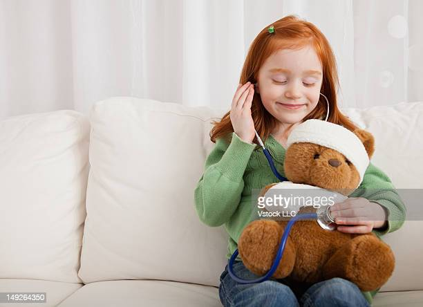 Girl (4-5) holding teddy bear with arm and head bandaged
