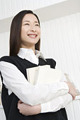 Girl holding textbooks, smiling, front view, low angle view