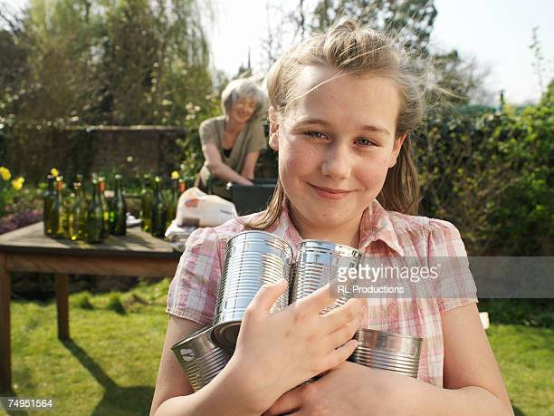 Girl (9-11) holding tin cans in garden, smiling, portrait
