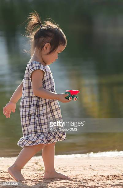 Girl holding toy while walk on beach