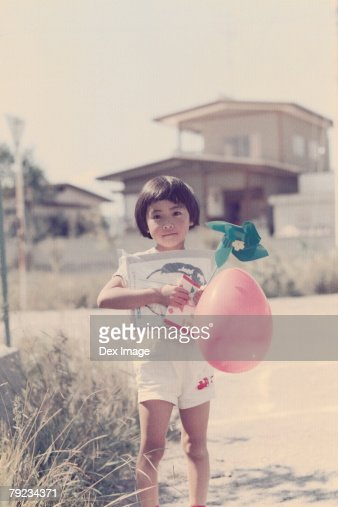Girl holding toys at the road side : Stock Photo