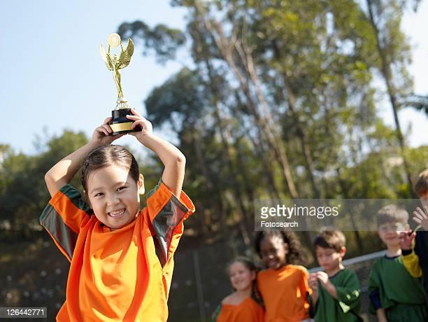 Girl holding trophy, soccer team in background (portrait)