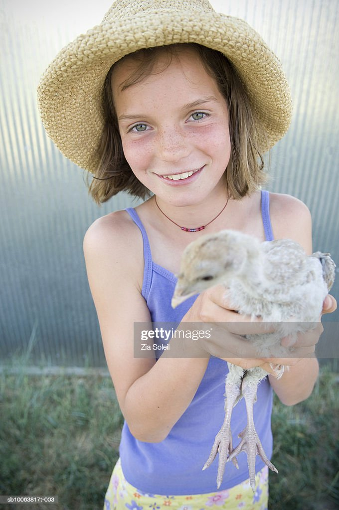 Girl  (10-11) holding turkey chick, smiling, portrait : Stock Photo