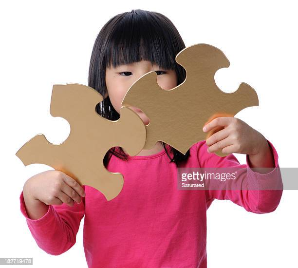 Girl Holding Two Gold Puzzle Pieces