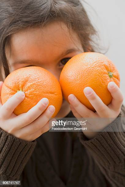 Girl holding two oranges in front of her face