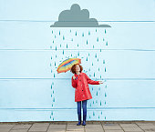 Girl holding umbrella with cartoon rain cloud