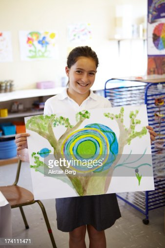 Girl holding up a painting in school art class : Stock Photo