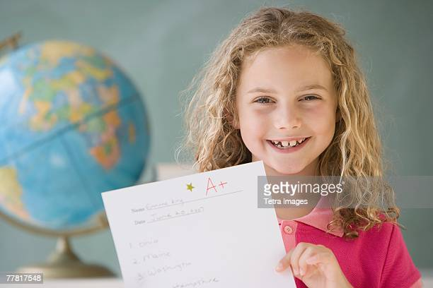 Girl holding up A plus paper in classroom