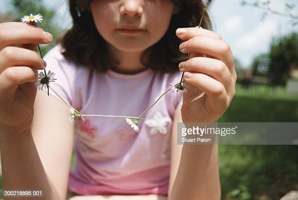 Girl (7-9) holding up daisy chain, close-up
