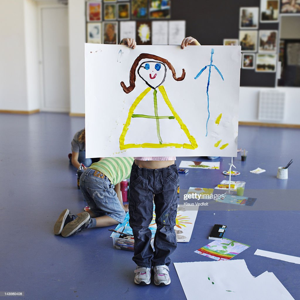 Girl holding up her drawing