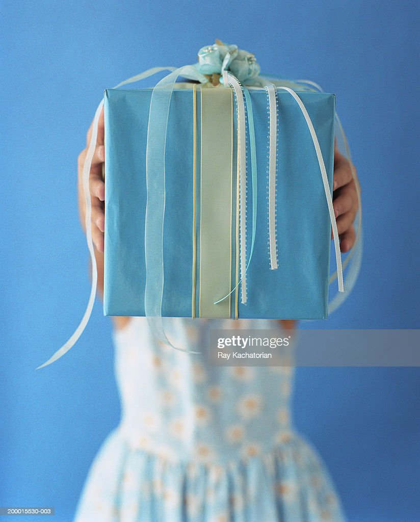 Girl (5-7) holding up present  with blue and white ribbons : Stock Photo