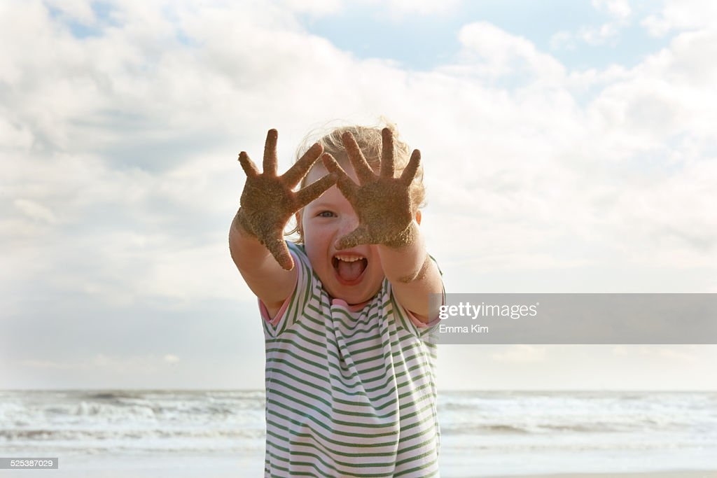 Girl holding up sandy hands on beach, Camber Sands, Kent, UK