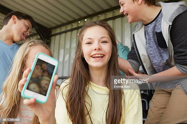 Girl holding up smartphone selfie of friends in shelter