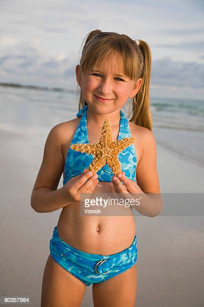 Girl holding up starfish, Florida, United States