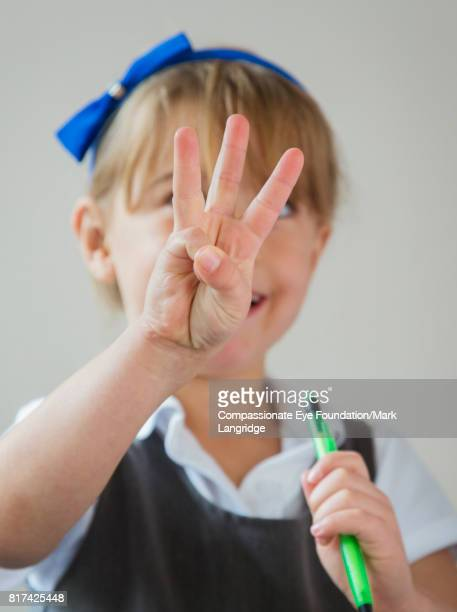 Girl holding up three fingers in kitchen