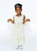Girl (2-4) holding up tier on dress, smiling, portrait