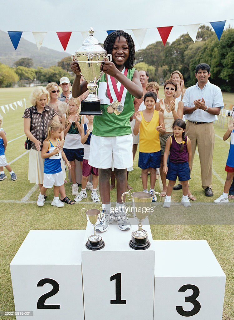 Girl (8-10) holding up trophy on winners podium, smiling