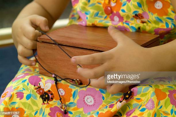 Girl holding wooden box, close-up, midsection, unknown person