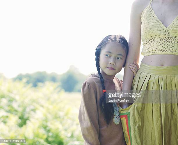 Girl (7-9) holding young woman's arm outdoors