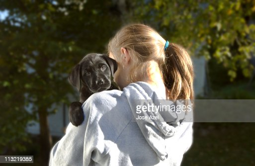 A girl holds a baby black labrador retriever puppy over her shoulder outdoors on a sunny afternoon in Maine.