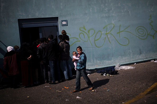 A girl holds a baby in her arms outside a passenger terminal used as a shelter for refugees and migrants at the Piraeus harbour in Athens on March 21, 2016. A total of 1,662 migrants have landed on...