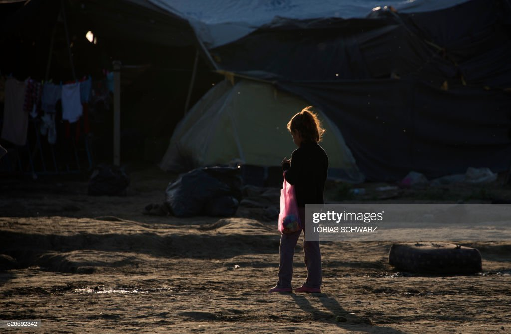 A girl holds a bag at a makeshift camp for migrants and refugees at the Greek-Macedonian border near the village of Idomeni on April 30, 2016. Some 54,000 people, many of them fleeing the war in Syria, have been stranded on Greek territory since the closure of the migrant route through the Balkans in February. / AFP / TOBIAS
