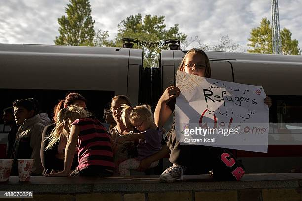A girl holds a banner to welcome migrants arriving on an ICE highspeed train of Deutsche Bahn from Munich near Berlin on September 13 2015 in...