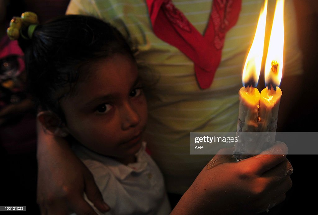 A girl holds a candle during a mass in celebration of San Jeronimo, the patron saint of Masaya, 30 km from Managua, on September 30, 2012. AFP PHOTO/Hector RETAMAL