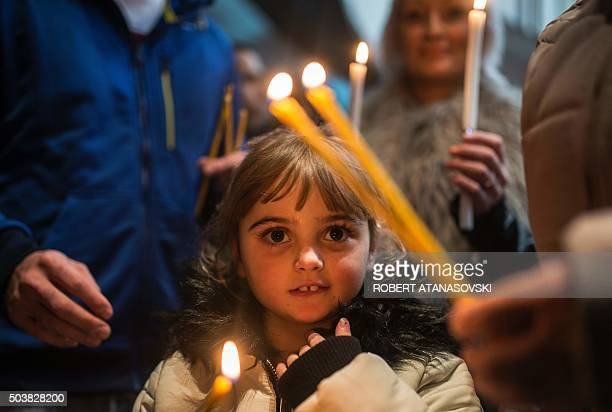 A girl holds a candle during a religious mass to celebrate the Orthodox Christmas at the Cathedral of St Clement in Skopje on January 7 according to...