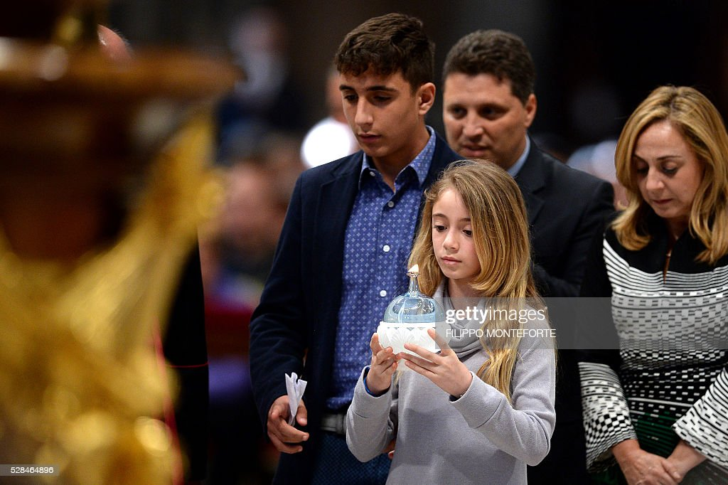 A girl holds a candle during the prayer vigil 'To Dry the Tears' for people in suffering, to mark the Catholic feast of Ascension on May 5, 2016 at the Saint Peter Basilica in Vatican. / AFP / FILIPPO