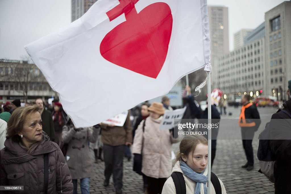 A girl holds a flag of the 'Coeur de Jesus' (Jesus heart) in a march against same-sex marriage on January 13, 2013 in Paris. Tens of thousands march in Paris on January 13 to denounce government plans to legalise same-sex marriage and adoption which have angered many Catholics and Muslims, France's two main faiths, as well as the right-wing opposition. The French parliament is to debate the bill -- one of the key electoral pledges of Socialist President -- at the end of this month.