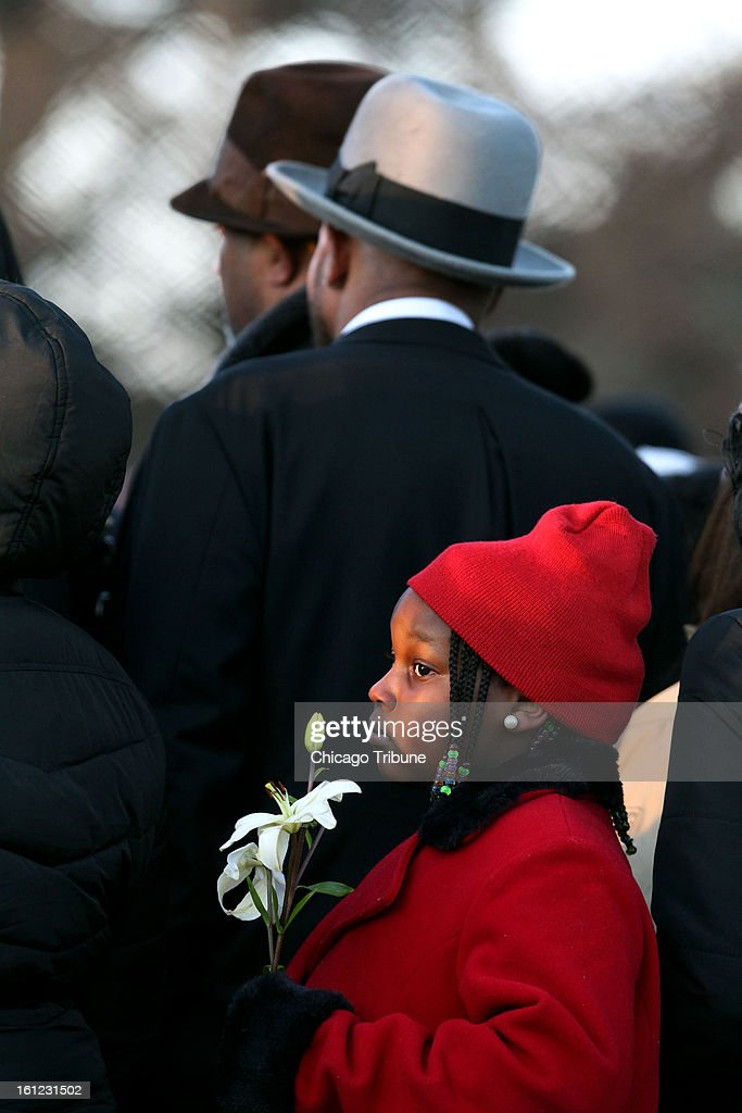 A girl holds a flower as 15-year-old Hadiya Pendleton is laid to rest at Cedar Park Cemetery in Riverdale, Illinois, on Saturday, February 9, 2013.