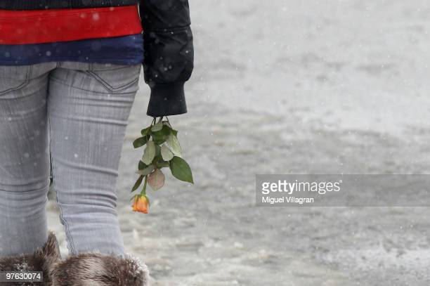 A girl holds a flower in her hand during the commemoration ceremony in front of the Albertville School on March 11 2010 in Winnenden Germany Tim...