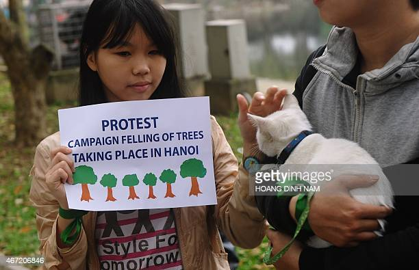 A girl holds a placard as she joins a rally protesting against a treefelling plan by the municipal authorities in Hanoi on March 22 2015 Vietnam...