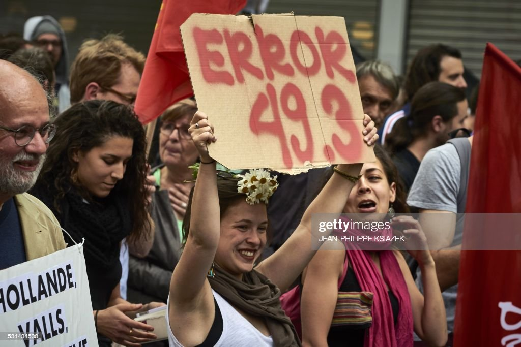 A girl holds a placard reading 'Error 49.3' during a demonstration against the government's planned labour reform, on May 26, 2016 in Lyon, central eastern France. The French government's labour market proposals, which are designed to make it easier for companies to hire and fire, have sparked a series of nationwide protests and strikes over the past three months. Masked youths clashed with police in Paris and striking workers blockaded refineries and nuclear power stations on May 26, 2016 as an escalating wave of industrial action against labour reforms rocked France. KSIAZEK