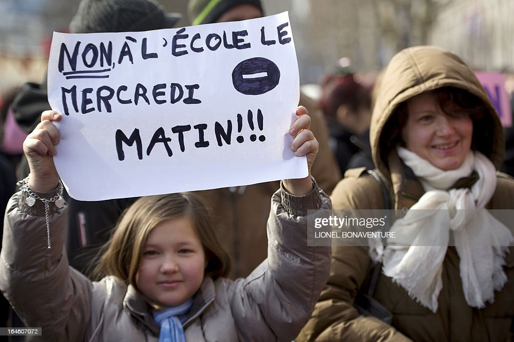A girl holds a placard reading 'No to school on wednesday morning' during a demonstration against the application for the 2013-2014 schoolyear of a reform law increasing the class time of primary school students in front of Paris' city hall, on March 25, 2013, as Paris' municipal council gathers to vote the law's application. AFP PHOTO / LIONEL BONAVENTURE