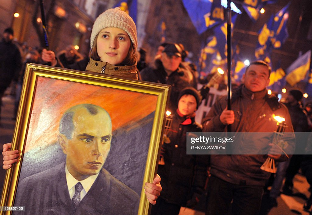 A girl holds a portrait of Stepan Bandera (L) in front of nationalists holding torches and flags during a march in Kiev on January 1, 2013, as they mark the 104th anniversary of the birth of Stepan Bandera. Bandera was a Ukrainian politician and one of the leaders of Ukrainian national movement in western Ukraine, who headed the Organization of Ukrainian Nationalists (OUN). Bandera was an activist, a scout, and eventually the leader of the Ukrainian nationalist movement and was personally responsible for a series of terrorist acts against Polish and Ukrainian civilians committed in interwar Poland.