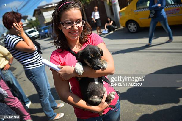 A girl holds a puppy newly adopted from an animal shelter owned by local authorities of Bucharest on September 13 2013 Romanian lawmakers voted...