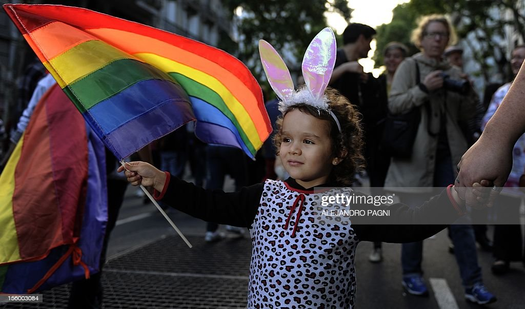 A girl holds a Rainbow flag of the LGBT movement during the XXI Gay Pride Parade, at Mayo square in Buenos Aires on November 10, 2012. AFP PHOTO / Alejandro PAGNI