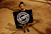 A girl holds a sign as she protests the shooting of Michael Brown August 21 2014 in Ferguson Missouri Crowds continue to gather to march along...