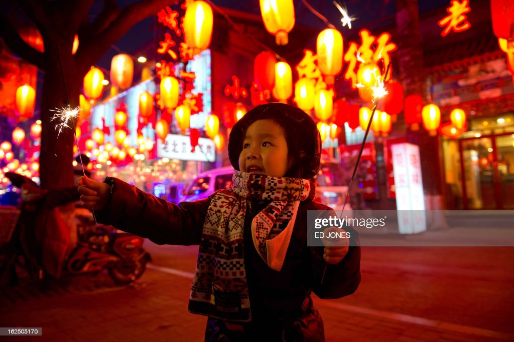 A girl holds a sparkler on a street in Beijing during the lantern festival, which marks the end of celebrations for the Chinese new year period, on February 24, 2013. China celebrated the traditional lantern festival with food and fireworks as millions of migrant workers flowed back to the cities and smog blanketed a large part of the country. AFP PHOTO / Ed Jones