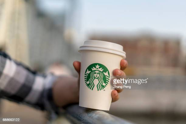 A girl holds a Starbucks coffee cup on a bridge Starbucks cup According to the report of the second quarter in 2017 the revenue of Starbucks was $53...