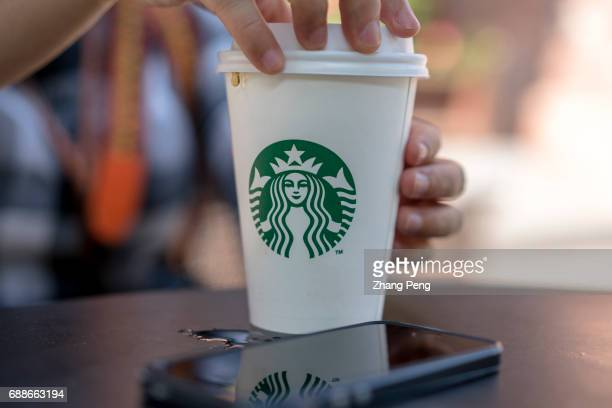 A girl holds a Starbucks coffee cup resting at roadside table According to the report of the second quarter in 2017 the revenue of Starbucks was $53...