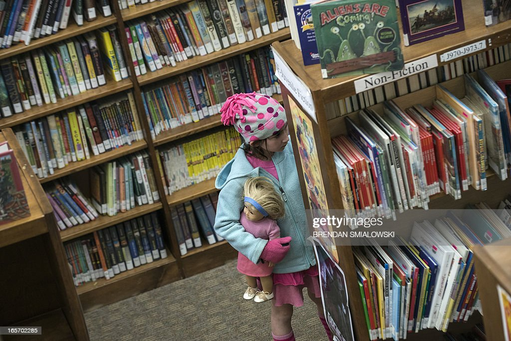 A girl holds an American Girl doll while looking at books in the Cherrydale Branch of the Arlington Library April 4, 2013 in Arlington, Virginia. The Arlington library is expanding their offerings to include items beyond books including American Girl dolls. AFP PHOTO/Brendan SMIALOWSKI